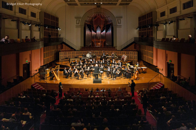 World Premiere of 'First Light at Uluru' for Wind Symphony with 25 extra players positioned throughout the audience.