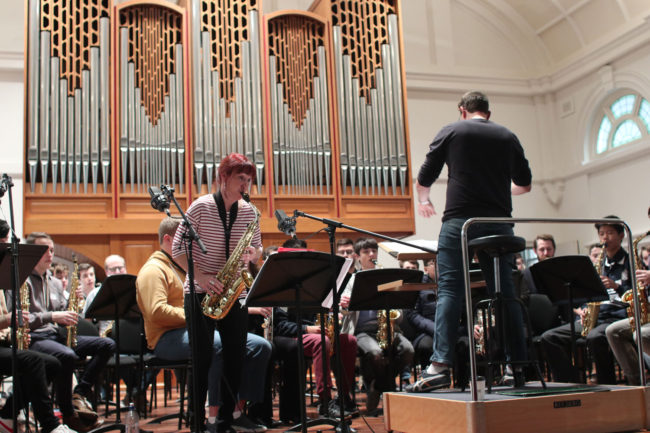 Rehearsal of Mark Phillips's saxophone concerto What If? for 100 saxes.